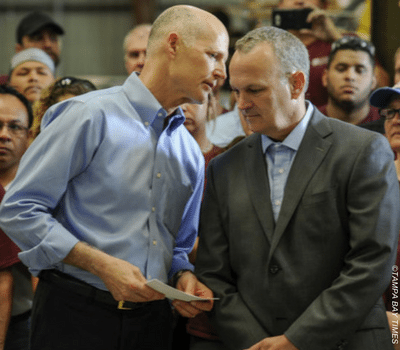 Gov. Scott whispers in House Speaker Corcoran's ear
